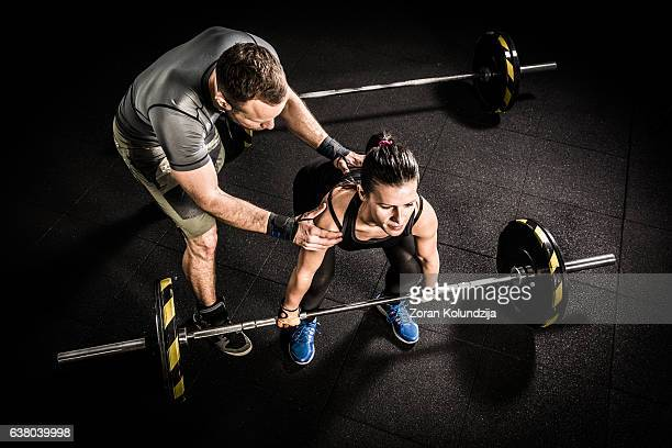 Young woman and fitness instructor on cross training in gym