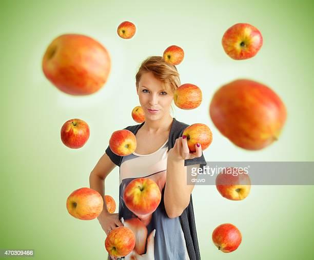 Mujer joven y volando Manzanas