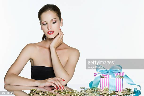 Young woman and gift box of coins