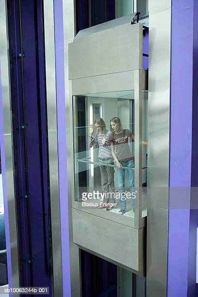 young woman and girl (10-13) in elevator and looking down - blasius erlinger stock pictures, royalty-free photos & images