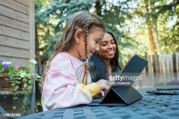 young woman and girl using digital tablet - education stock pictures, royalty-free photos & images