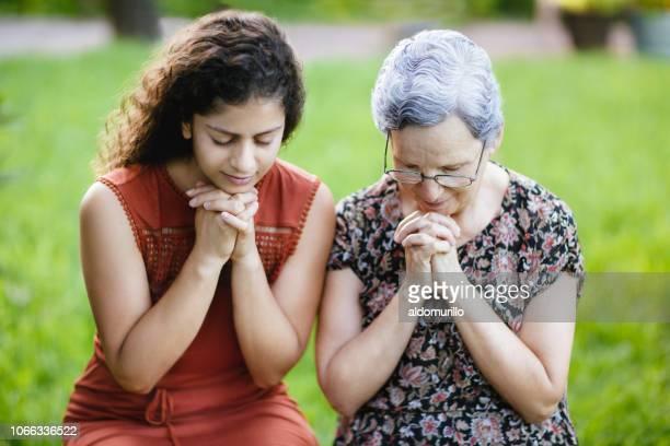 若い女性と祖母の手で一緒に祈って - キリスト教 ストックフォトと画像
