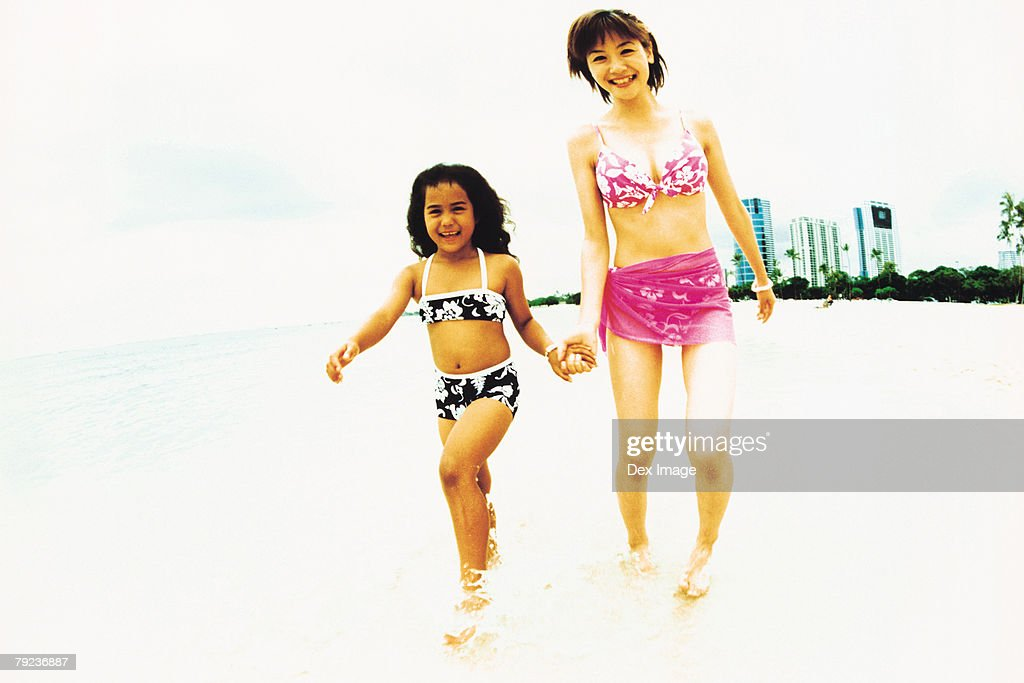 Young woman and Hawaiian girl walking in shallow waters : Stock Photo