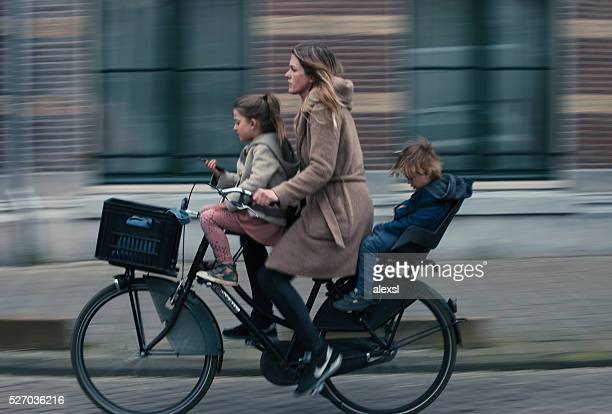 Young woman and her children riding a bicycle in Amsterdam