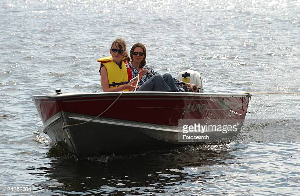 Young woman and her daughter in a motor boat\