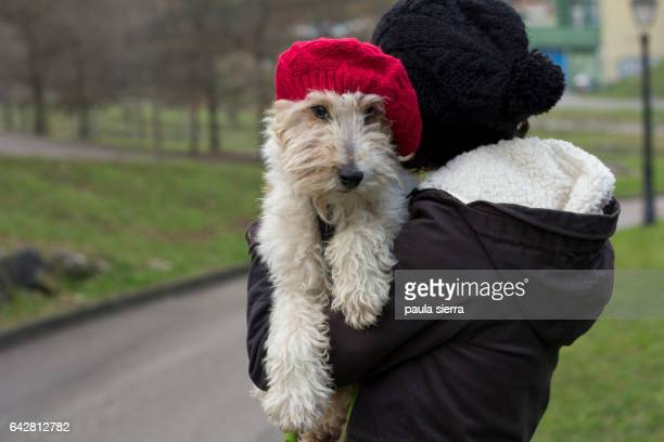 A young woman and her dog are in a park