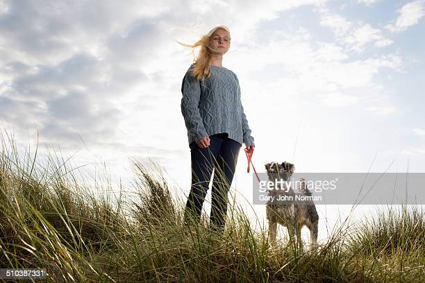 young woman and her dog at the beach. - loyalty stock pictures, royalty-free photos & images