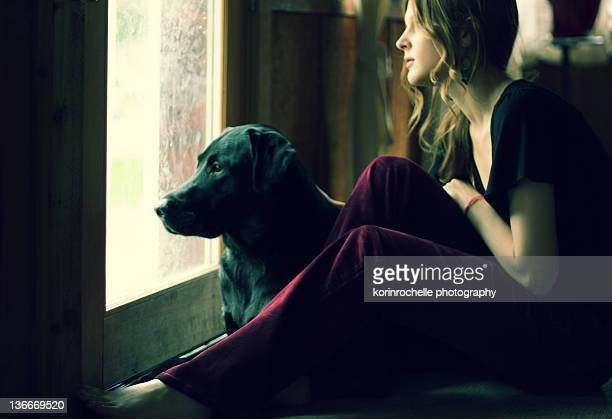 Young woman and her dog looking out of window