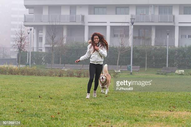 mujer joven y su perro corriendo y jugando - pjphoto69 fotografías e imágenes de stock