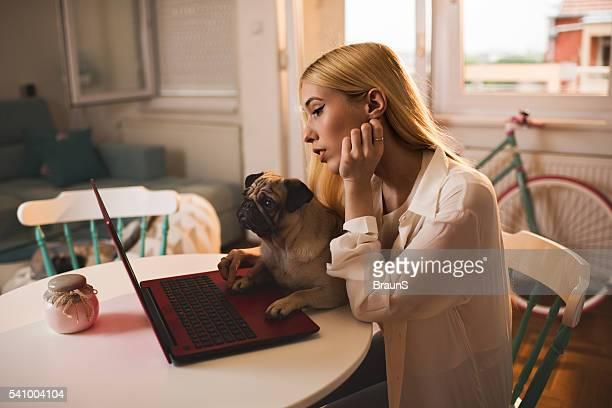 Giovane donna e il suo cane usando il il computer portatile a casa.