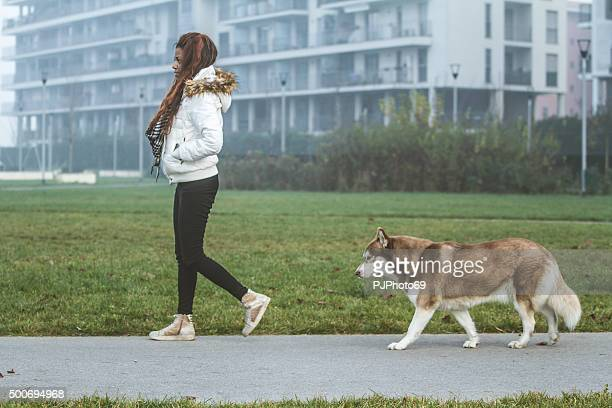Young woman and her dog walking