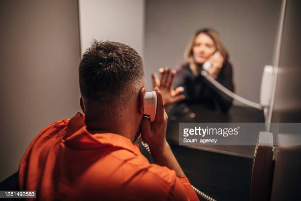 young woman and her husband sitting in prison visiting room - prison stock pictures, royalty-free photos & images