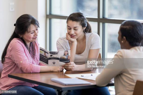 young woman and her mom review bank pamphlet - flyer leaflet stock pictures, royalty-free photos & images