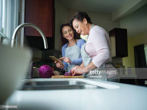 a young woman and her mother trying a recipe together - homemaker stock pictures, royalty-free photos & images