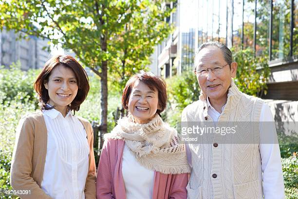 Young woman and her parents smiling on street