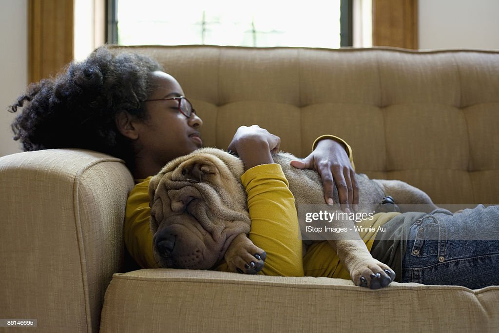 A young woman and her Shar-Pei napping on a couch : Stock Photo