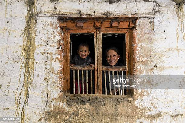 A young woman and her son child are looking out of the window of a farmhouse