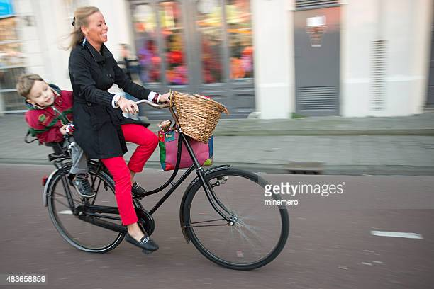 Young woman and her son riding a bicycle in Amsterdam.
