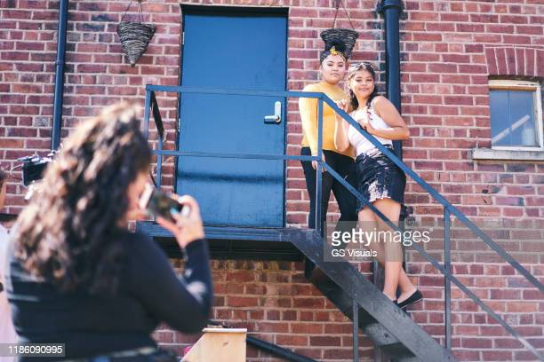 young woman and her teenage sister being photographed  on fire escape - mini skirt stock pictures, royalty-free photos & images
