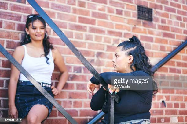 young woman and her teenage sister on fire escape - mini skirt stock pictures, royalty-free photos & images