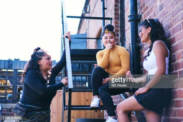 young woman and her teenage sisters chatting on fire escape - mini skirt stock pictures, royalty-free photos & images