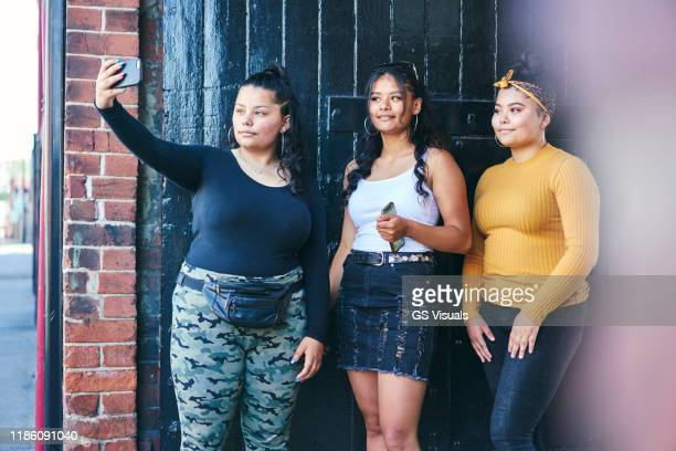 young woman and her teenage sisters posing for smartphone selfie in building entrance - mini skirt stock pictures, royalty-free photos & images