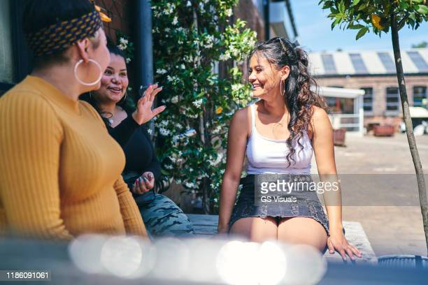 young woman and her teenage sisters sitting on outdoor table chatting - mini skirt stock pictures, royalty-free photos & images