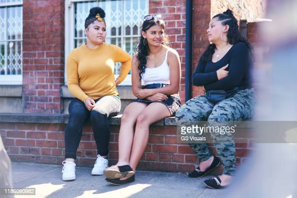 young woman and her teenage sisters sitting on wall talking - mini skirt stock pictures, royalty-free photos & images