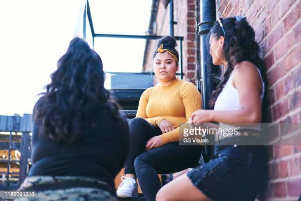 young woman and her teenage sisters talking on fire escape - mini skirt stock pictures, royalty-free photos & images
