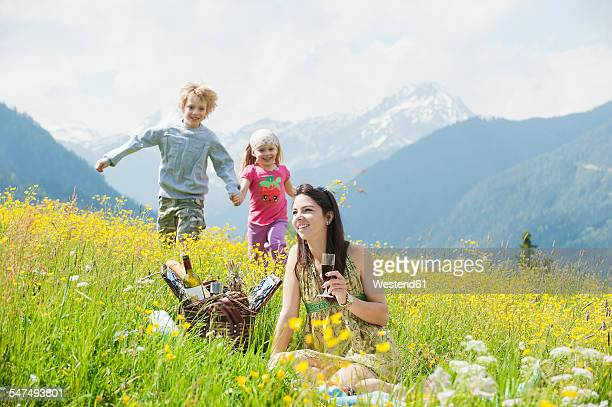 Young woman and her two children having fun on alpine meadow