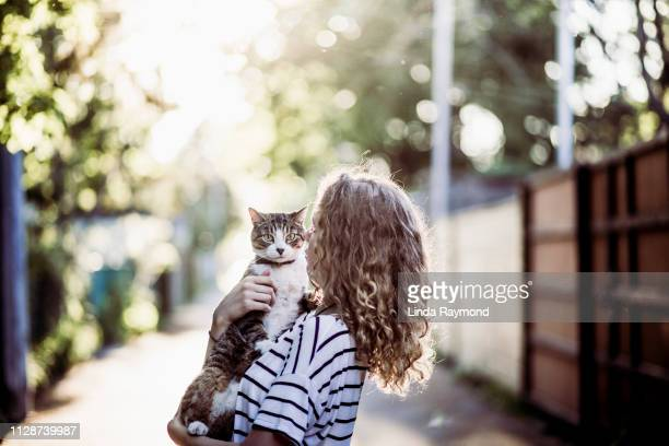 young woman and here cat in an alley - alley stock pictures, royalty-free photos & images
