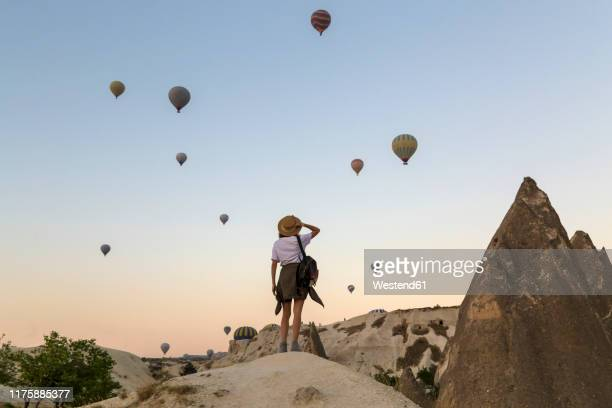 young woman and hot air ballons, goreme, cappadocia, turkey - turkey middle east stock pictures, royalty-free photos & images