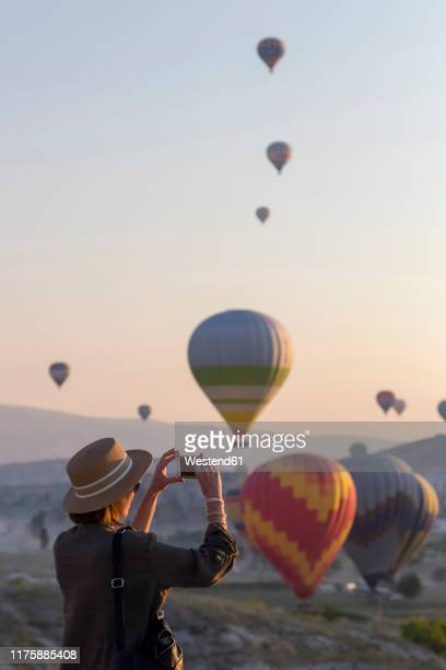 young woman and hot air ballons, goreme, cappadocia, turkey - hot women pics ストックフォトと画像