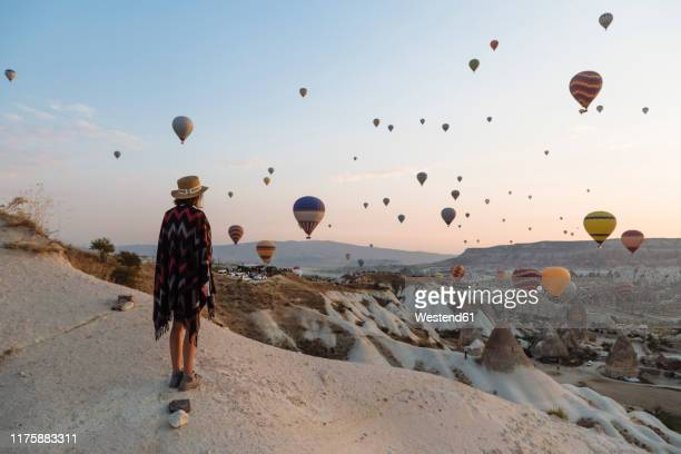 young woman and hot air balloons in the evening, goreme, cappadocia, turkey - majestic stock pictures, royalty-free photos & images
