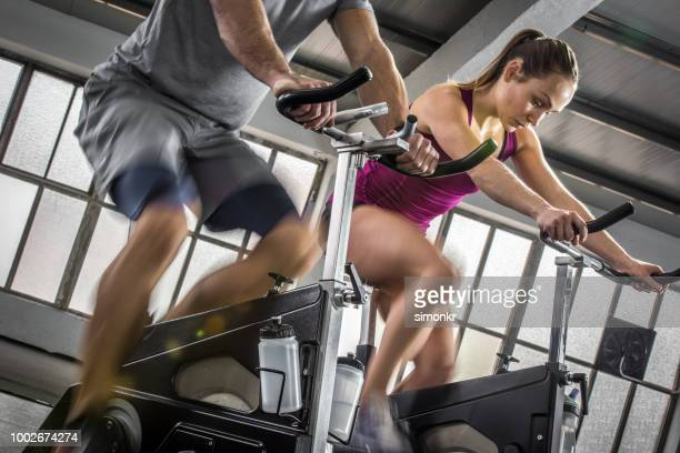 young woman and instructor exercising in gym - exercise bike stock photos and pictures