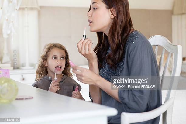 young woman and little girl applying lip gloss at dressing table - mimica fotografías e imágenes de stock