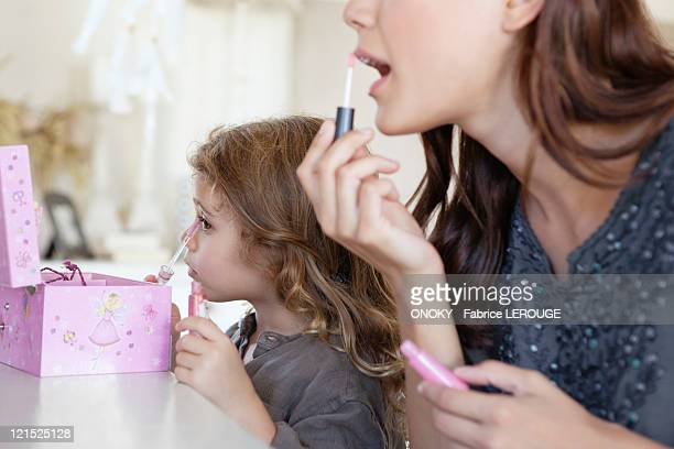Young woman and little girl applying make-up at dressing table