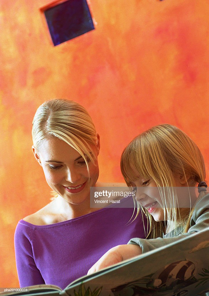Young woman and little girl looking at book, head and shoulders : Stockfoto