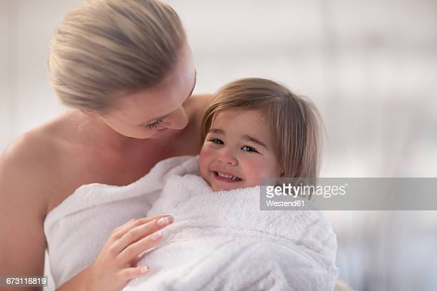 young woman and little girl wrapped in a towel - mother daughter towel stock photos and pictures