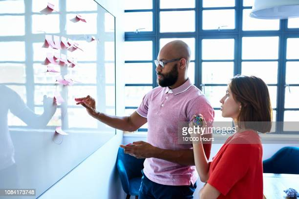 young woman and male colleague writing ideas on adhesive notes - putting stock pictures, royalty-free photos & images