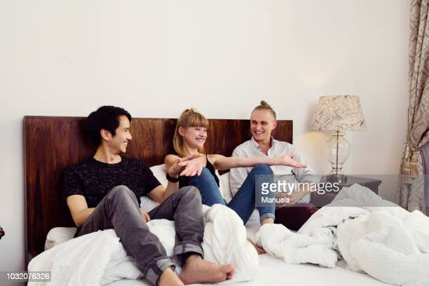 young woman and male friends sitting chatting on bed - three people fotografías e imágenes de stock