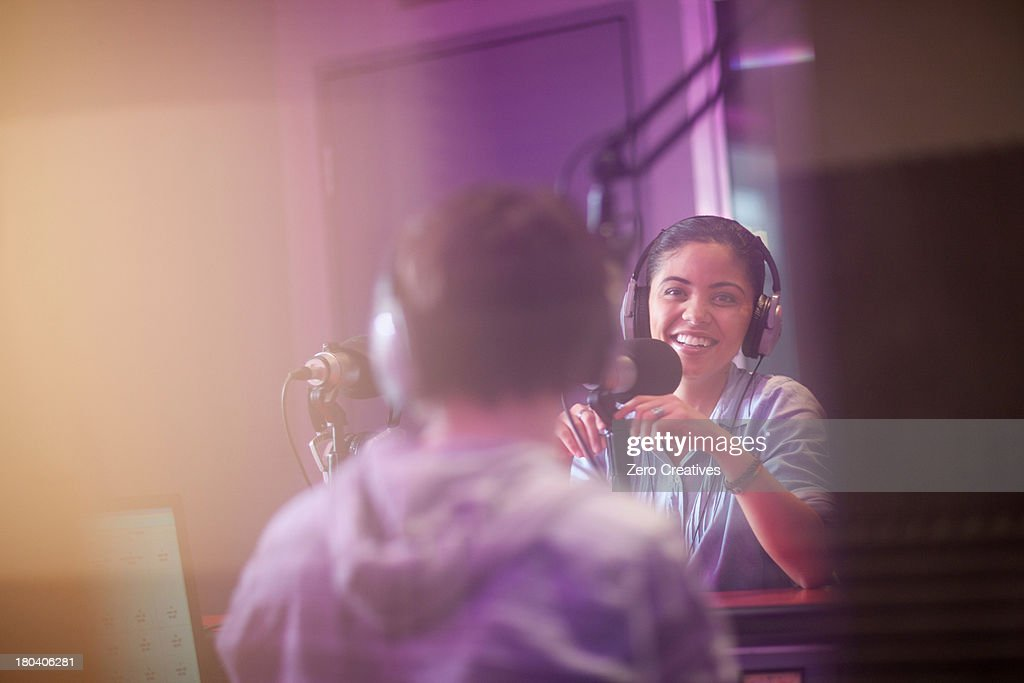 Young woman and man broadcasting in recording studio : Stock Photo