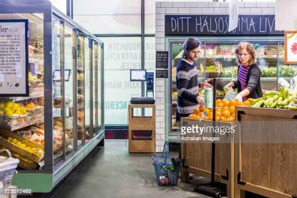 Young woman and man buying oranges in supermarket