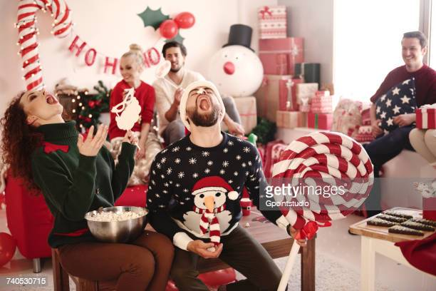 Young woman and man catching popcorn in open mouths at christmas party