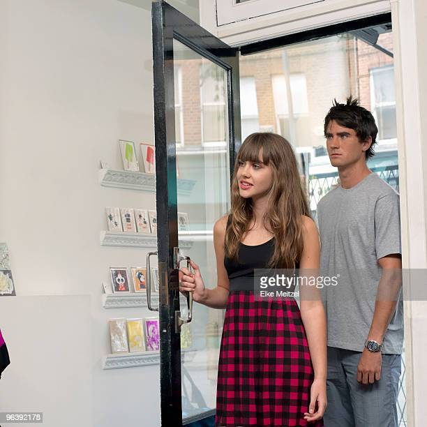 Young woman and man entering a shop