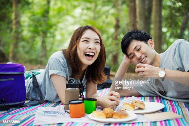Young woman and man having a picnic in a forest.