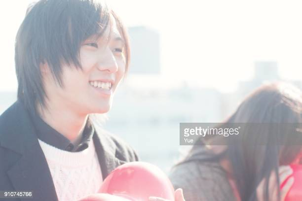 Young woman and man hugging red heart balloon on sunny winter day