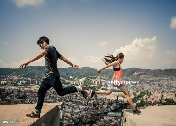 junge frau und mann springen und üben parkour - le parkour stock-fotos und bilder
