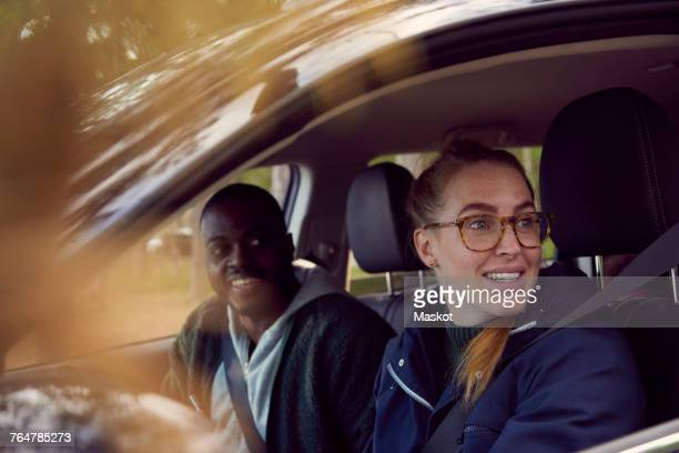 Young woman and man looking away while sitting in car