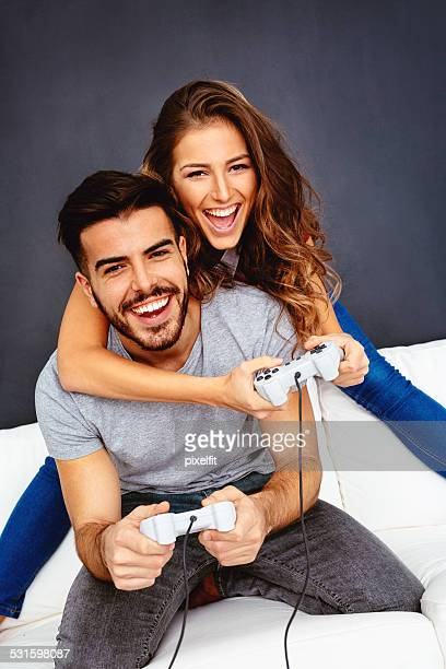 Young woman and man playing video game and smiling